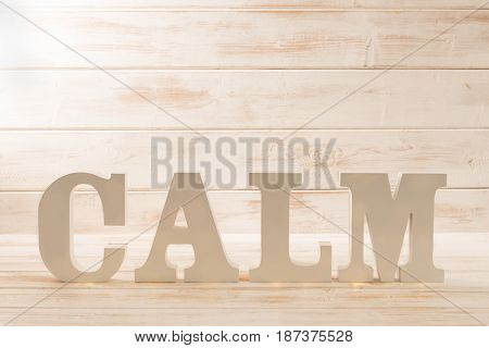 Letters spelling CALM over a wooden panel background