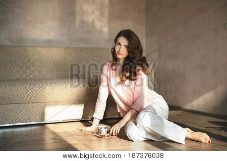 Beautiful young woman siting in the floor at home and drinking coffee or tea.