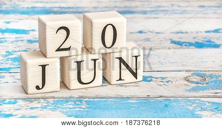 June 20th. Wooden cubes with date of 20 June on old blue wooden background.