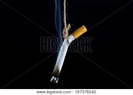 Anti Tobacco, Cigarette was hanged with a rope on dark background.