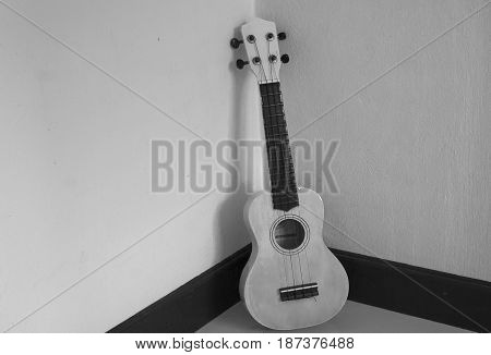 Musical instrument ukulele guitar on gray tile floor at room corner. (Black and White filter effect)