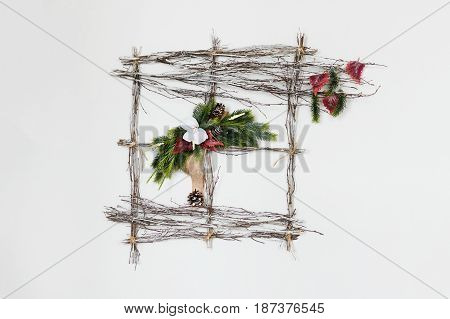 Abstract New Year's composition from willow twigs, fir branches, oak leaves, cones, natural mats and artificial flowers of orchid on gray background. Christmas concept.