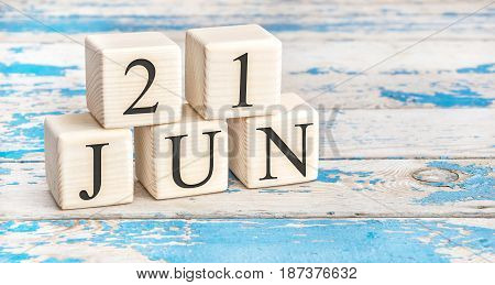 June 21st. Wooden cubes with date of 21 June on old blue wooden background.