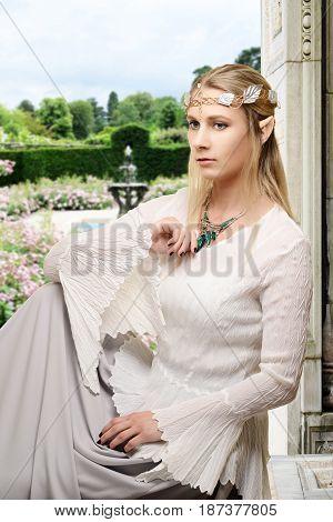 female high elf sitting in flower garden