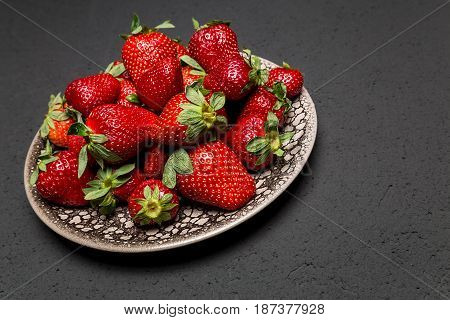 fresh ripe useful fruit strawberry in a clay bowl closeup on a black background