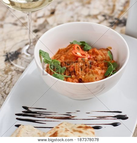Chicken fillet slices fried in spicy cream sauce with tortilla bread served in white bowl with glass of wine, knife and fork on napkin on marble table
