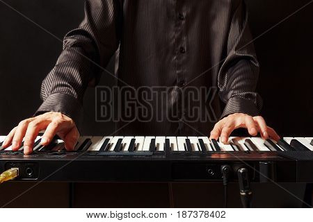 Musician playing the electronic synth on a black background