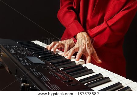 Pianist play the keys of the synthesizer on a black background