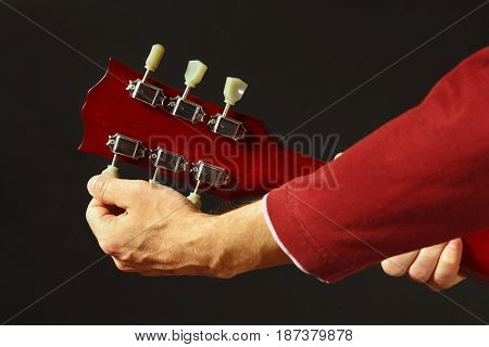 Artist tunes the guitar on a dark background
