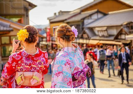 Kyoto, Japan - April 24, 2017: Japanese women wearing Japanese traditional kimono take selfie after visiting of Kiyomizu-dera Temple. Matsubara dori pedestrian shopping street on defocused background.