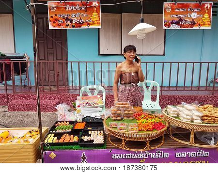 KAMPHAENG PHET THAILAND - MAY 6 : unidentified asian woman with Thai traditional clothing using mobile phone in Nakhon Chum street market on May 6 2017 in Kamphaeng Phet Thailand.