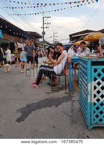 KAMPHAENG PHET THAILAND - MAY 6 : unidentified asian beautiful woman taking selfie in Nakhon Chum street market on May 6 2017 in Kamphaeng Phet Thailand.