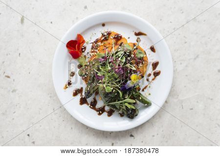 Overhead shot of vegetable salad meal with brown sauce on round white plate on a white stone surface