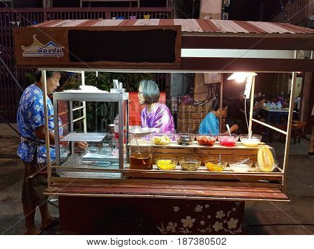 KAMPHAENG PHET THAILAND - MAY 6 : unidentified asian woman with Thai traditional clothing selling dessert in Nakhon Chum street market on May 6 2017 in Kamphaeng Phet Thailand.