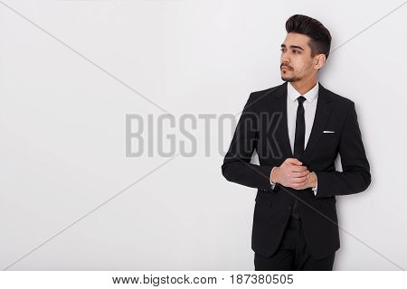 Young Businessman In Black Suit On A White Background. Confident Man Looking Away From The Camera.
