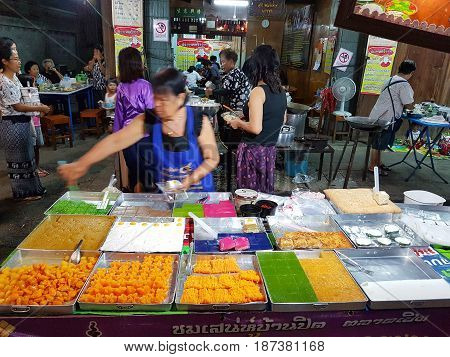 KAMPHAENG PHET THAILAND - MAY 6 : unidentified asian woman with Thai traditional clothing selling variuos desserts in Nakhon Chum street market on May 6 2017 in Kamphaeng Phet Thailand.