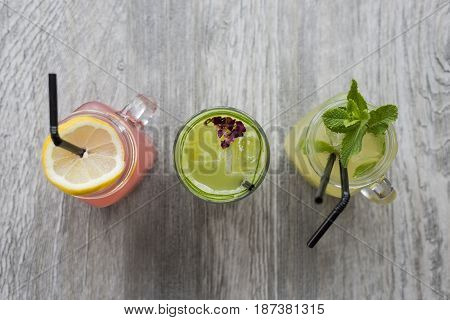 Natural Fruit Drinks In Masonry Jars On Wooden Surface
