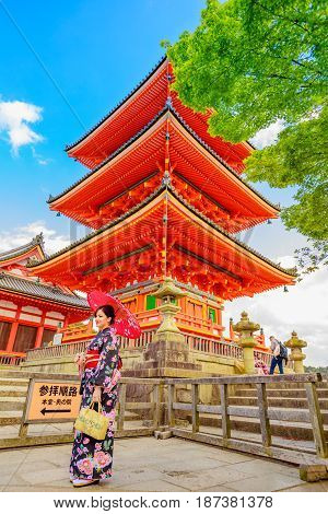 Kyoto, Japan - April 24, 2017: woman wear kimono and parasol standing in red Pagoda of Kiyomizu Temple or Kiyomizudera, one of the most celebrated temples of Japan and popular landmark in Kyoto.