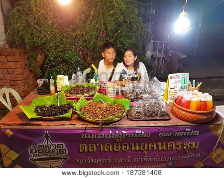 KAMPHAENG PHET THAILAND - MAY 6 : unidentified asian couple with Thai traditional clothing selling fried bamboo caterpilla in Nakhon Chum street market on May 6 2017 in Kamphaeng Phet Thailand.