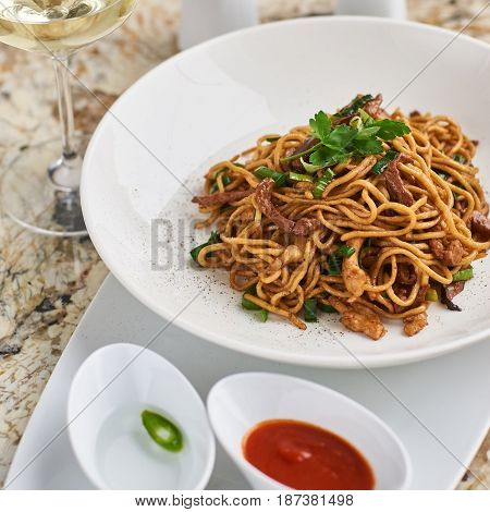 Flat egg noodles with duck meat, chicken, shiitake mushrooms served on white plate with white garlic and red spicy sauce