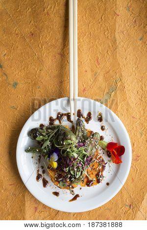 Chopsticks On Plate Of Salad Over Textured Orange Surface