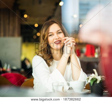 Happy beautiful woman sitting in restaurant with double exposure