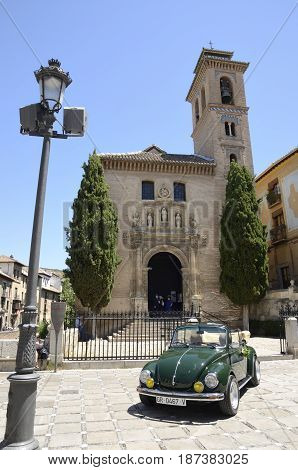 GRANADA, SPAIN . MAY 20, 2017: Green small car in front the church of Saint Ana in Granada Andalusia Spain