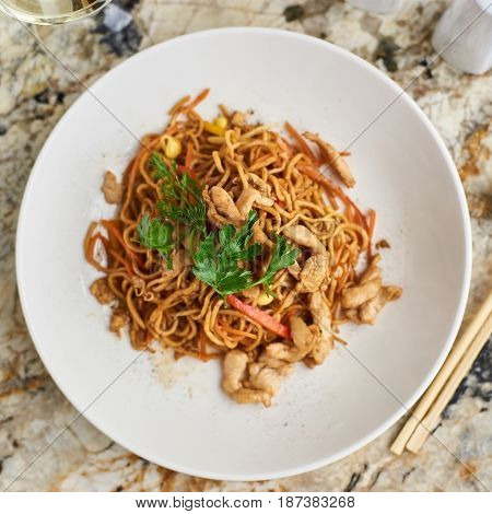 Thin egg noodles with chicken slices served on white plate with white garlic and red spicy sauce