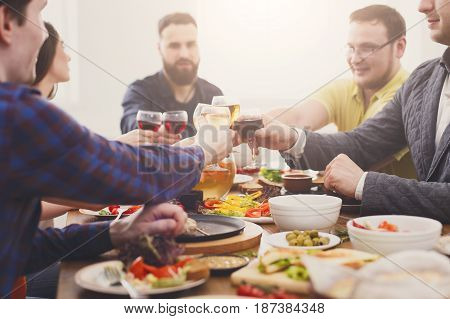 People clink glasses, saying toast, cheers at party dinner table in cafe, restaurant or at home. Young cute friends company celebrate with organic food at wooden table indoors.