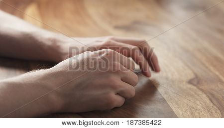 Young man hands waiting nervous at the table, wide photo