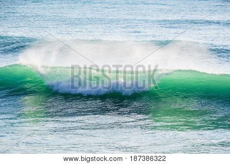 Turquoise wave in ocean and Sun rays