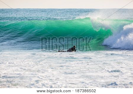 Surfing on turquoise wave in ocean. Wave and surfer