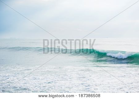 Green wave in ocean and Sun rays