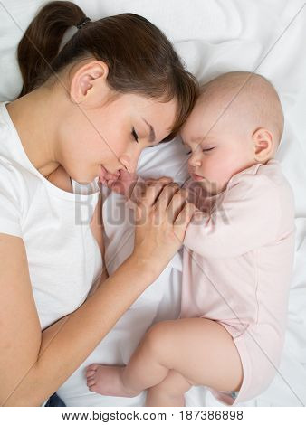 Mother with newborn baby sleeping on bed at home. Top view close up.