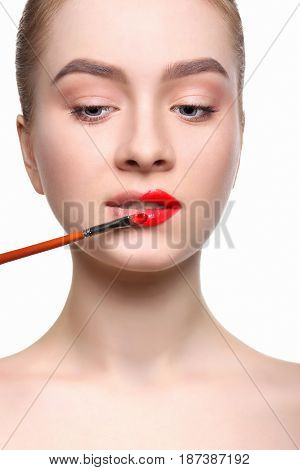 Make-up artist apply lipstick with brush. Close-up of female model face with fashion glossy red makeup, beauty concept