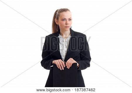 young charming girl in black jacket looks straight and holding a Tablet is isolated on a white background