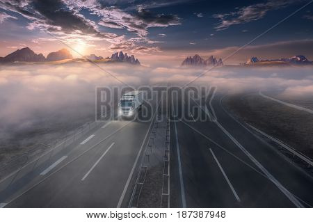 Delivery truck driving towards the mountain range at beautiful sunrise. Fast blurred motion drive on the straight freeway in beautiful foggy landscape. Freight scene with headlights on motorway.