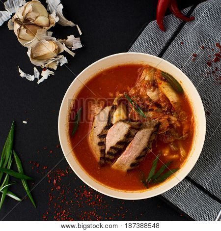 Korean cuisine. Spicy kimchi soup served in a bowl standing on black background.