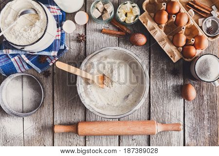 Baking background. Cooking ingredients for dough and bowl with flour on rustic wood.