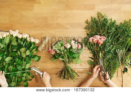Small business. Flowers delivery top view. Florists creating order, making rose bouquet in flower shop.