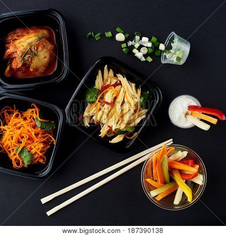 Korean cuisine. Set of salads on black background. Asparagus, korean carrot, kaktugi, fresh vegetable sticks and green onion.