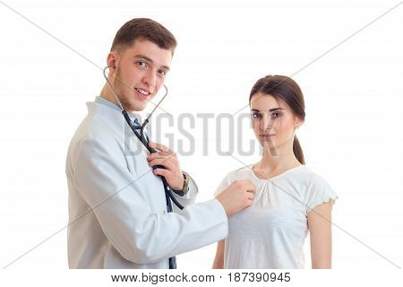 young smiling doctor looks straight stands near girls and listens to her heart with a stethoscope isolated on white background