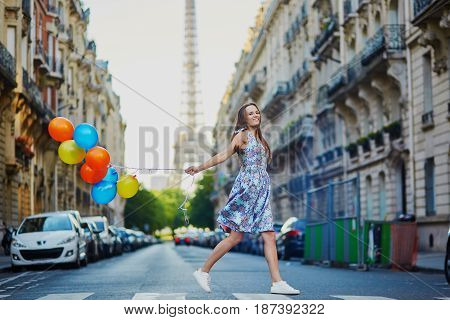 Beautiful Young Girl With Colorful Balloons Running Across The Street In Paris