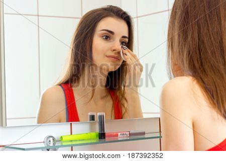 tender young girl standing in the bathroom front of the mirror and rubs lotion face close-up