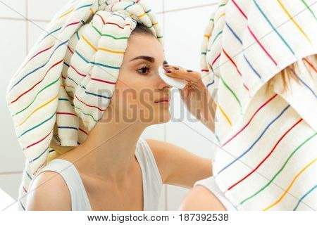 young girl with towel on the hair looks in the mirror and gently wipes her face with a cotton disk close-up