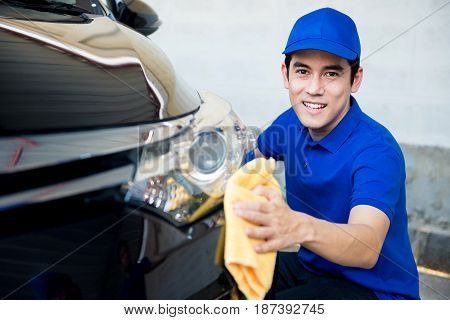 Young man polishing (cleaning) car with microfiber cloth - car detailing valeting and auto service concepts