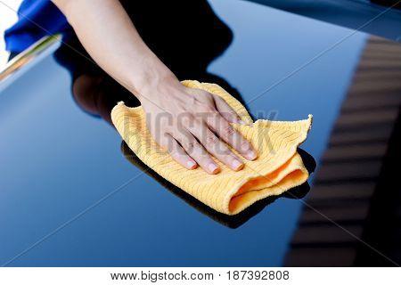 Hand with microfiber cloth polishing car bonnet