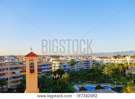 Panorama of the resort city of Torremolinos with a turret and a weather vane during sunset