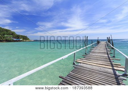 Wooden bridge pier leading to summer tropical sea with blue sky at Koh Samed Island famous tourist attraction in Rayong province Thailand.