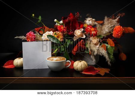 Cappuccino and beautiful flowers still life. Flower shop composition. Coffee cup, apple, fresh and bouquet on black wood background. Florist art and floral design concept, copy space on white